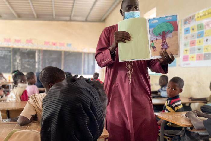 A teacher, holding a book, with his students inside the classroom