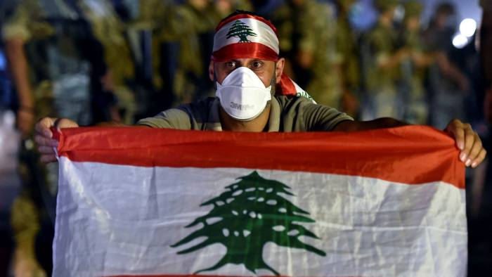 An anti-government protester poses with a national flag in front of Lebanese army soldiers during a protest in Jal El Dib, north of Beirut, on Sunday