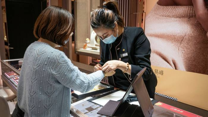 A customer tries on a gold bracelet at a jewellery store in Beijing, China