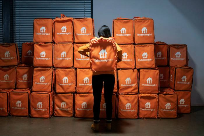 A delivery rider carries a customer's order in a Takeaway.com backpack inside the online food delivery company's distribution hub in Amsterdam