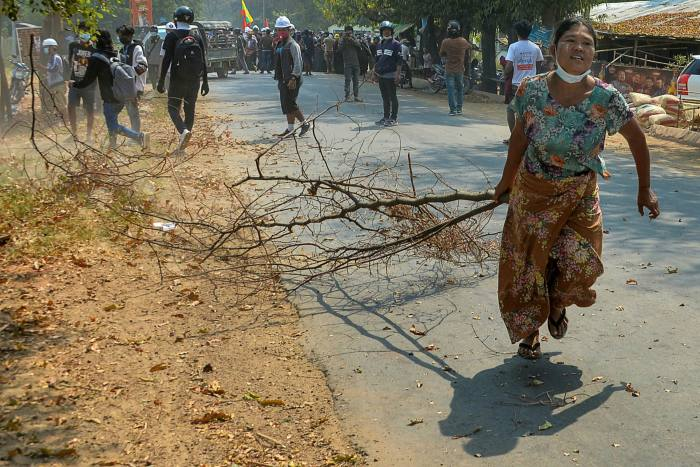 A protester drags a branch to block a road during a demonstration in Naypyidaw