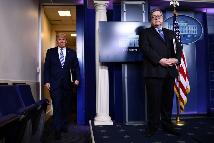 President Donald Trump arrives as attorney-general William Barr looks on during the daily coronavirus briefing at the White House