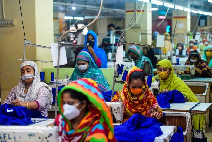 Labourers wear face masks in a garment factory in Dhaka.Bangladesh industry groups estimate that over half of its textile workforce has already been laid off