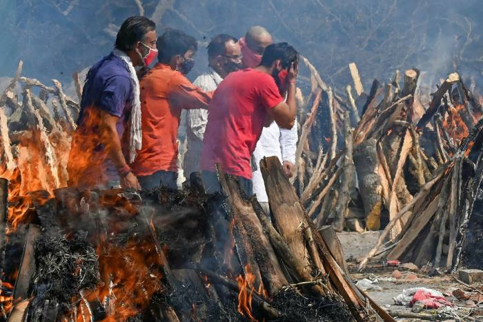 Mourners in India attend the cremation of a relative who died of Covid-19