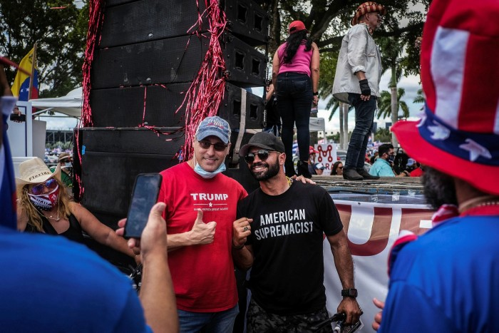 Facebook has had some limited success in tackling extremist hate groups, such as the Proud Boys. Enrique Tarrio, left, leader of the group, poses for a photo during a pro-Trump rally in Miami this week