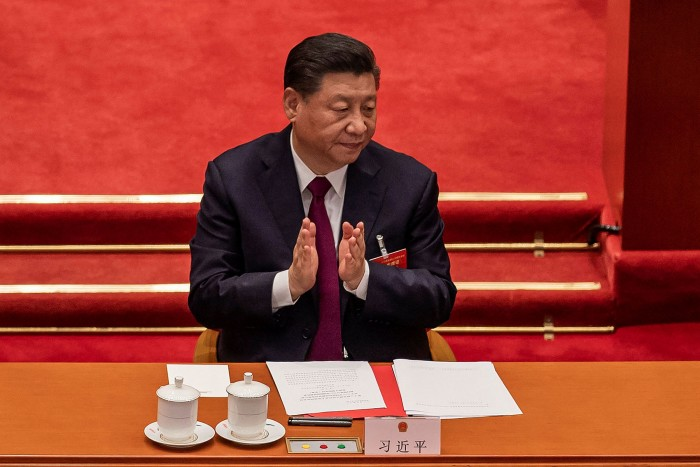 Xi Jinping applauds after the result of the vote on changes to Hong Kong's election system was announced in Beijing in March