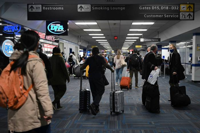 Passengers walk through a crowded terminal at Dulles International airport in Dulles, Virginia on December 27