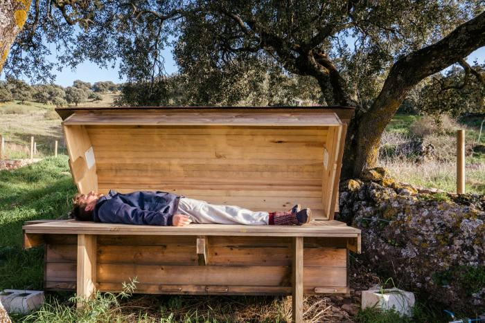 A guest listening to the meditative hum of hives on the 'bee bed' at La Donaira
