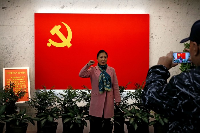 A woman poses for a photograph in front of a Communist flag at the museum of the first National Congress of the Communist Party of China in Shanghai
