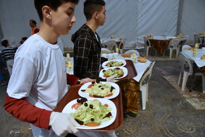 Volunteers serve meals to poor families at a charity centre in Algiers