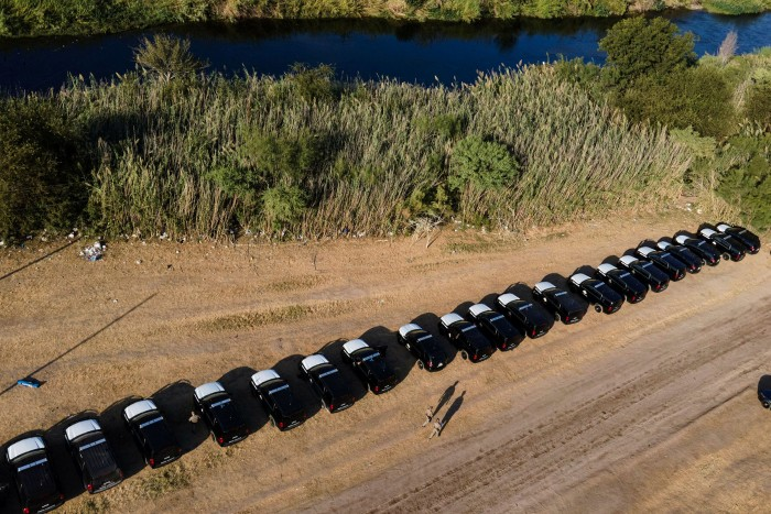 A line of vehicles from Texas state officials on the banks of the Rio Grande, near a migrant encampment