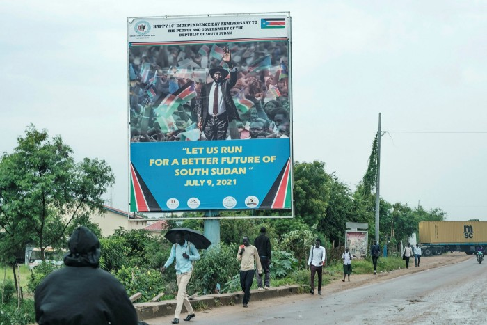 People pass a poster in Juba showing President Salva Kiir and celebrating 10 years of independence. The government of Kiir and his vice-president, Riek Machar, is racked with factionalism