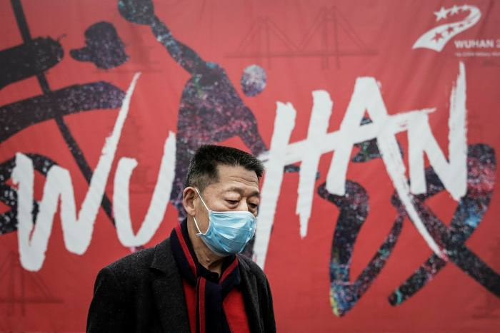 A man wears a mask while walking in January in the Chinese city of Wuhan — the epicentre of the pandemic