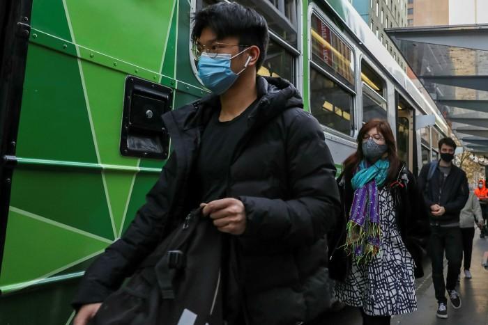 Los viajeros usan máscaras cuando salen de un tranvía en Melbourne el martes