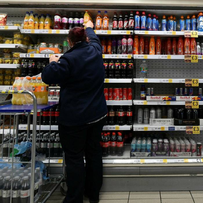 A staff member stocks shelves at a Tesco supermarket in central London