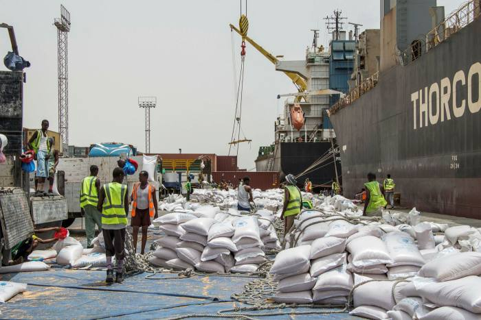 Workers unload food from a ship before loading trucks at Berbera port, in Somaliland