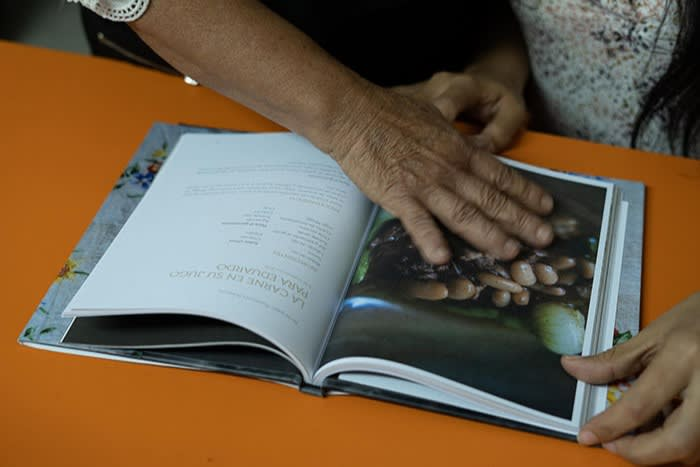 Rodríguez Peñuelas looks through the book 'Recipes to Remember'. She says of the idea of asking the authorities to aid the Rastreadoras' search for the disappeared: 'They won't help us — they're the same ones who are involved'