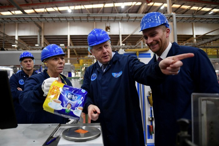 Boris Johnson weighs packaged tea bags during a general election campaign visit to the Tetley Tea Factory at Tata Global Beverages in Stockton-on-Tees, last November