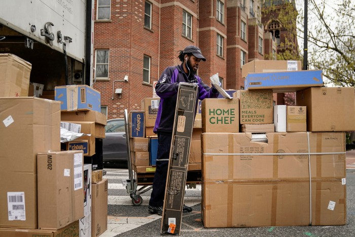 A delivery driver unloads boxes in  Washington. If a worker is classified as essential, they have few if any legal protections if they decide not to report for work