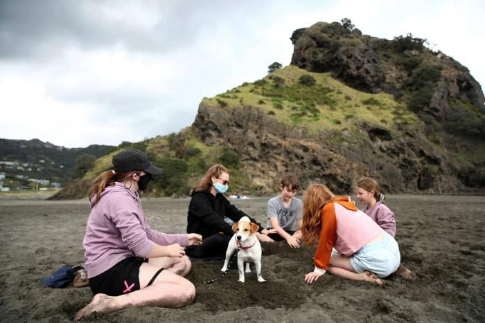 New Zealanders enjoy a picnic on Piha Beach in Auckland