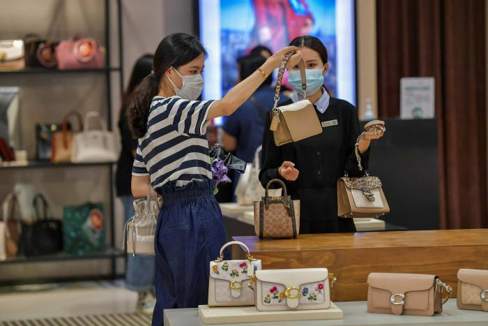 Tourists purchase bags at a duty-free shop in Haikou, Hainan