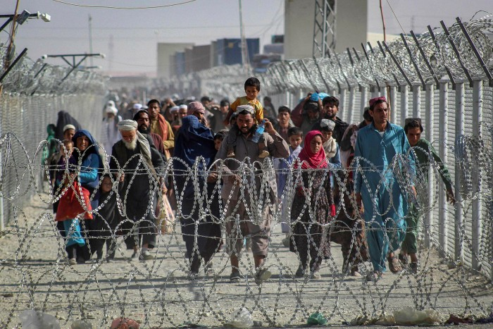 Afghans arrive at a border crossing with Pakistan