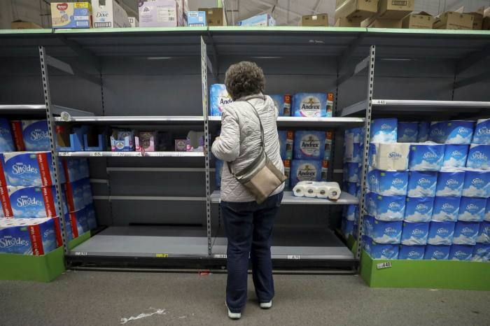 A customer selects an item from a nearly empty section of toilet paper rolls in an Asda supermarket in England