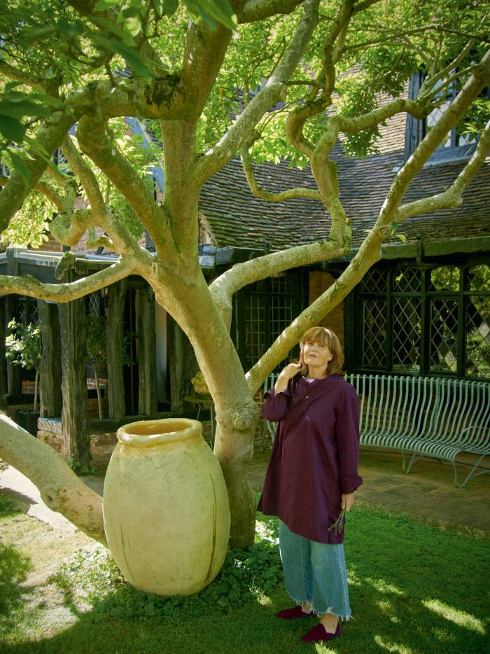 Ettedgui by a magnolia tree and an antique Andalouse pot at the entrance to her home