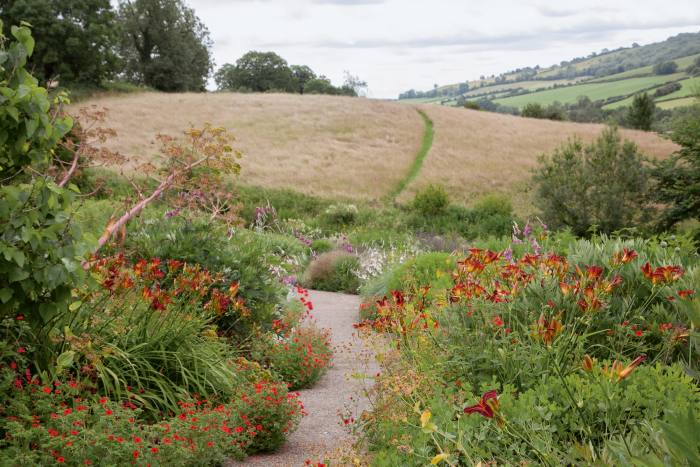 "The central path of the garden seen in summer, with vibrant reds of Potentilla ""Gibson's Scarlet"" and Hemerocallis ""Stafford"""