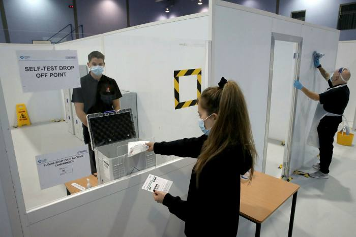 A student deposits her sample as she demonstrates how to take a coronavirus test at a walk-through testing centre at Glasgow Caledonian University