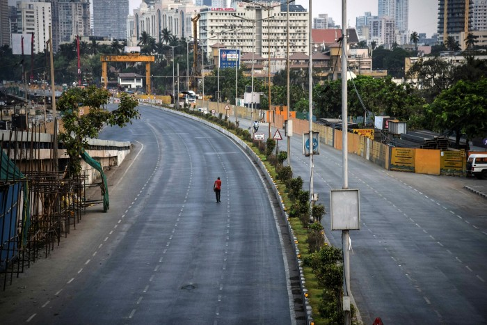 A man walks along a near-deserted street during a lockdown in April this year in Mumbai