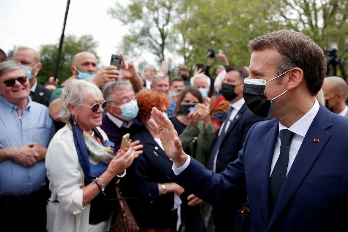 Emmanuel Macron greets voters at the polling station in Le Touquet on Sunday