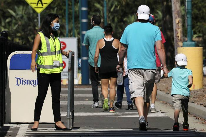 Peopleenter the Downtown Disney District in Anaheim, California, after it reopened following its closure over coronavirus