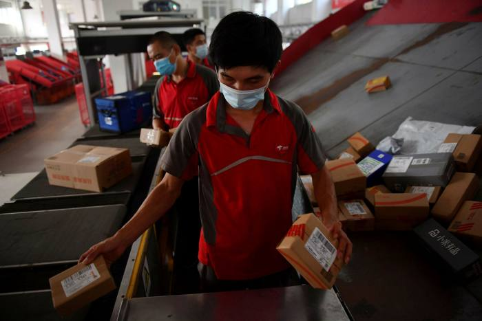 Delivery workers for Chinese ecommerce giant JD.com sort parcels at a distribution centre in Beijing