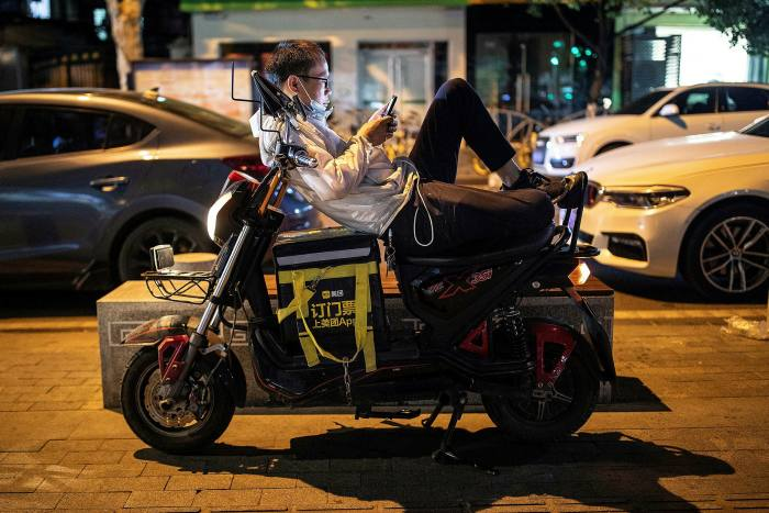 A Chinese delivery rider waits for orders in Wuhan