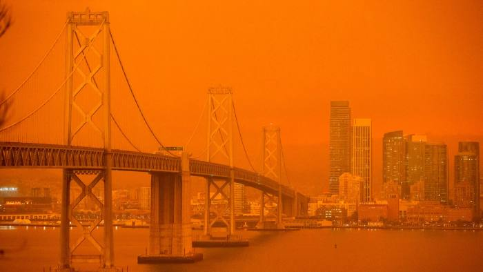 The San Francisco Bay bridge and city skyline are obscured in smoke and haze after wildfires ravaged surrounding California countryside last September