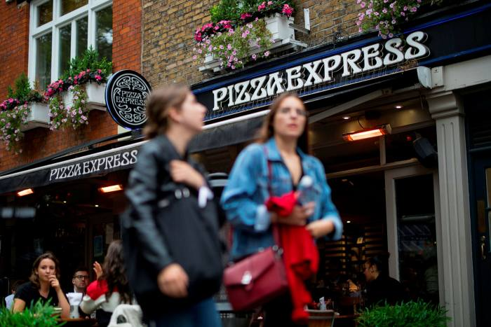 Pedestrians walk past a PizzaExpress restaurant in central London