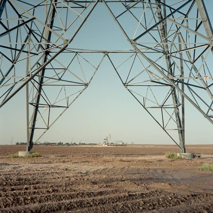 A pump jack produces oil beneath power lines near Midland, west Texas