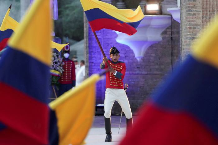 A soldier dressed in a historical uniform waves a Colombian flag at an event to mark the bicentennial of the country's first constitution