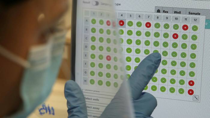 A scientist views a screen showing test results for Covid-19, with the red dots a positive sample and the green dots a negative
