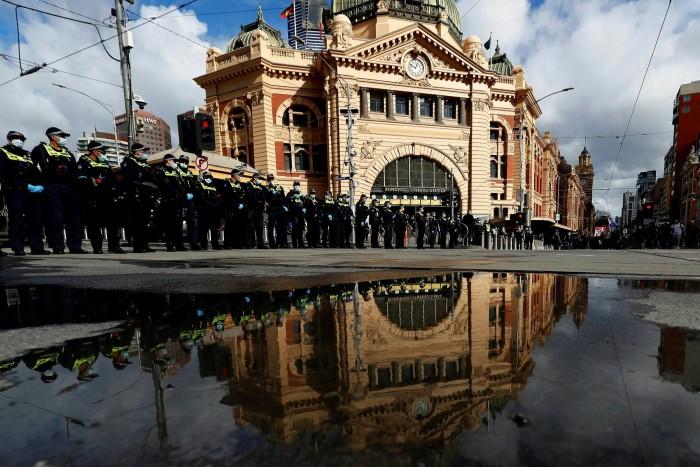 La policía de Victoria forma una línea cerca de la estación de tren de Flinders Street en Melbourne antes de una protesta contra el bloqueo