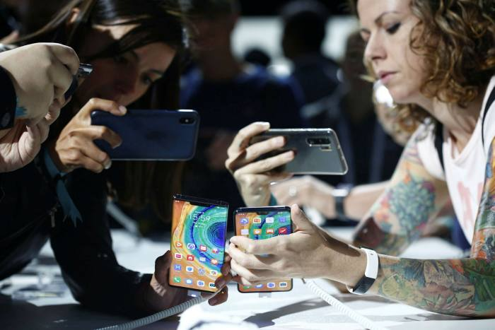 Attendees inspect Huawei's Mate 30 smartphones during the device's unveiling in Munich, Germany, last September