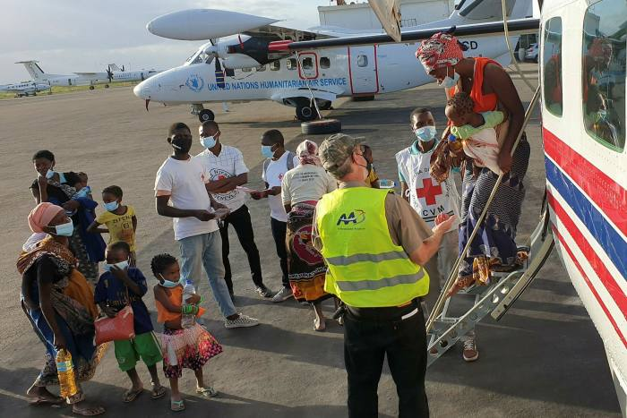 People fleeing fighting in and around Palma arrive after being evacuated by plane to the provincial capital, Pemba