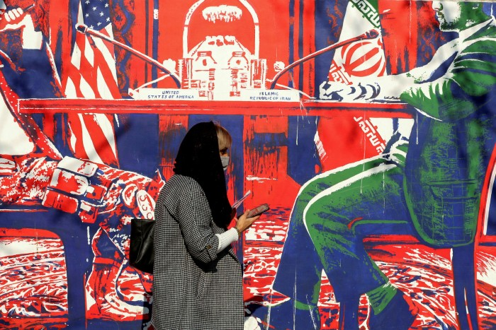 An Iranian woman wearing a protective mask walks past a mural in Tehran