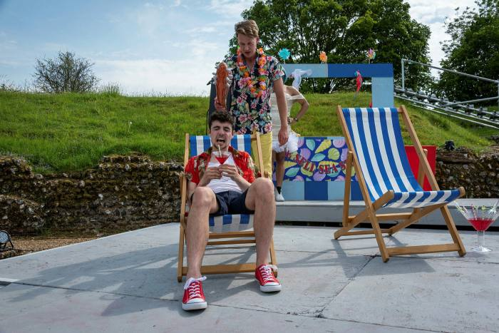 One man standing behind the other in a deck chair