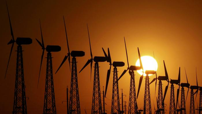 The sun sets behind power-generating turbines of a local wind farm in the settlement of Mirnyi, Crimea