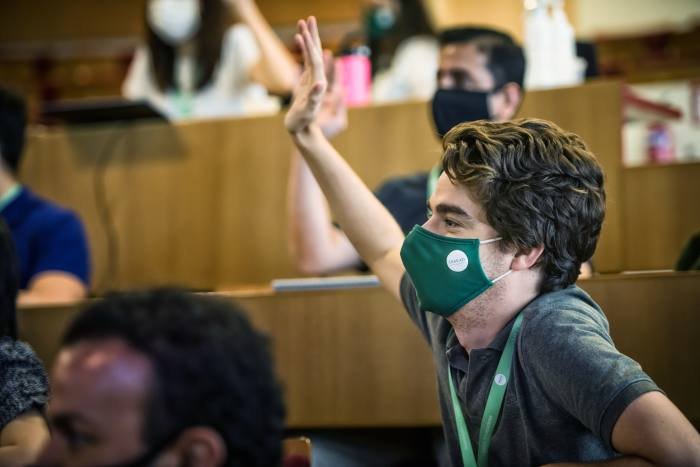 A male student with a face mask, raising his hand in class
