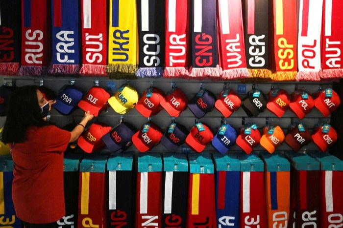 A worker arranges football merchandise in a shop at Wembley Stadium ahead of Euro 2020
