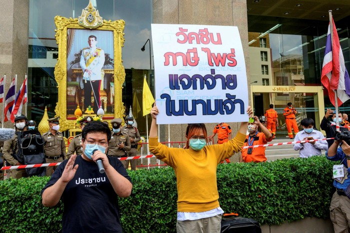 Pro-democracy activist Parit 'Penguin' Chiwarak (L) speaks as fellow activist Bencha Apan holds a sign that reads, 'Vaccine from the working class taxpayers, distributed in the name of the crown' during a protest outside the offices of  Siam BioScience in Bangkok in January