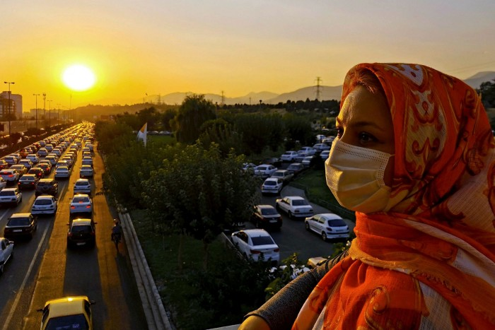 A pedestrian wearing a mask returns home during rush hour in Tehran, where insufficient vaccine deployment sparks public anger